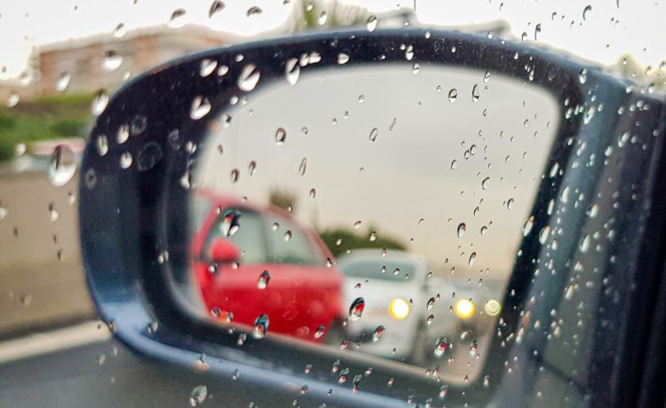 car side mirror with rain drops